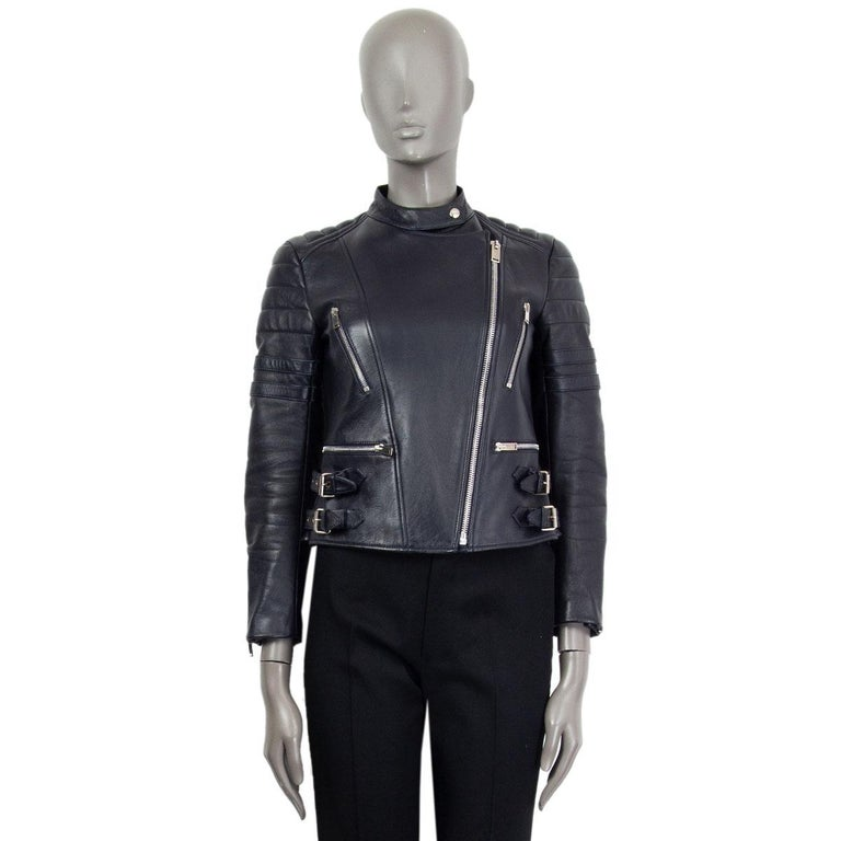authentic Céline biker jacket in midnight blue leather with front zipper pockets and decorative waist buckles. Closes on the front with a zipper. Lined in red viscose (100%). Padding is polyester (100%). Lining shows  some light stains along the