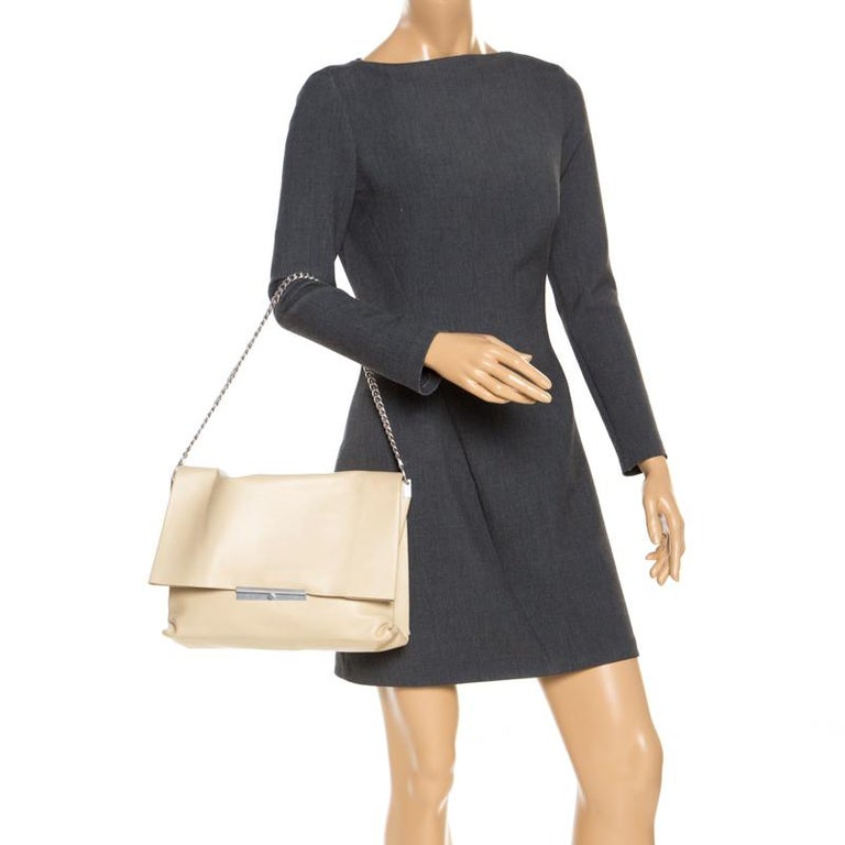 Carry along a mark of sophistication with this simple yet attractive Celine bag. It has been crafted in nude leather. The bag features a top handle and flap closure with silver-tone hardware detailing. The interior is suede-lined and has two open