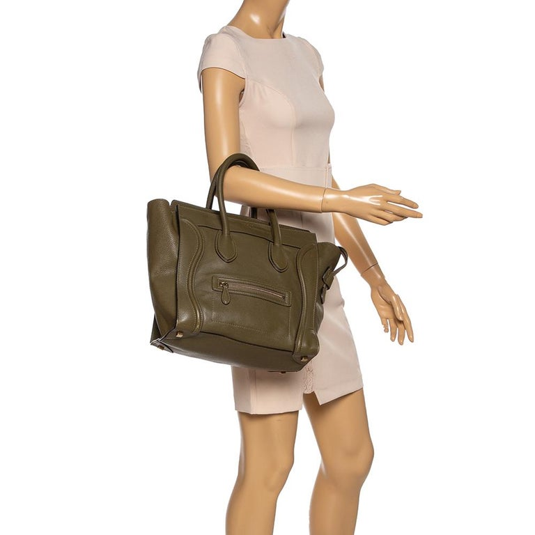 The mini Luggage tote from Celine is one of the most popular handbags in the world. This tote is crafted from leather and designed in an olive green shade. It comes with rolled top handles and a front zip pocket. The bag is equipped with a