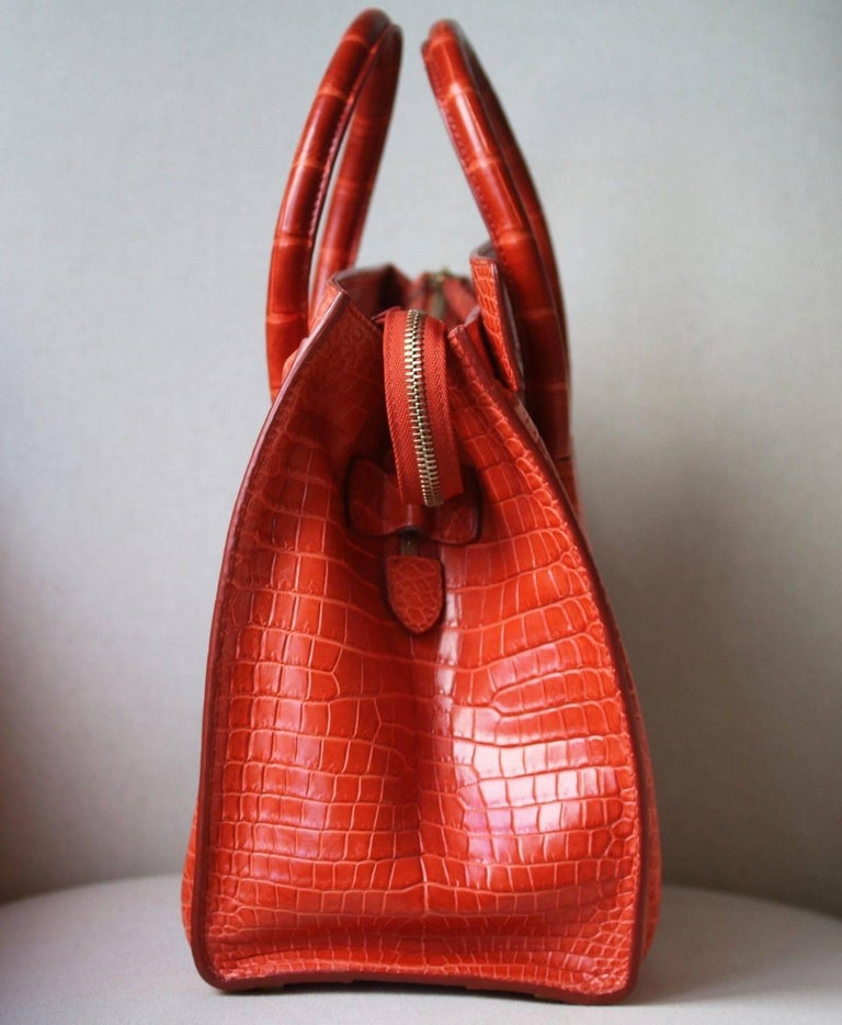 Celine Crocodile Handbag with Goldtone Hardware in beautiful crocodile leather in the most beautiful rich orange colour with tonal orange stitching.    Condition - Leather is still stiff and untarnished. Has full feeling of a new bag. Excellent
