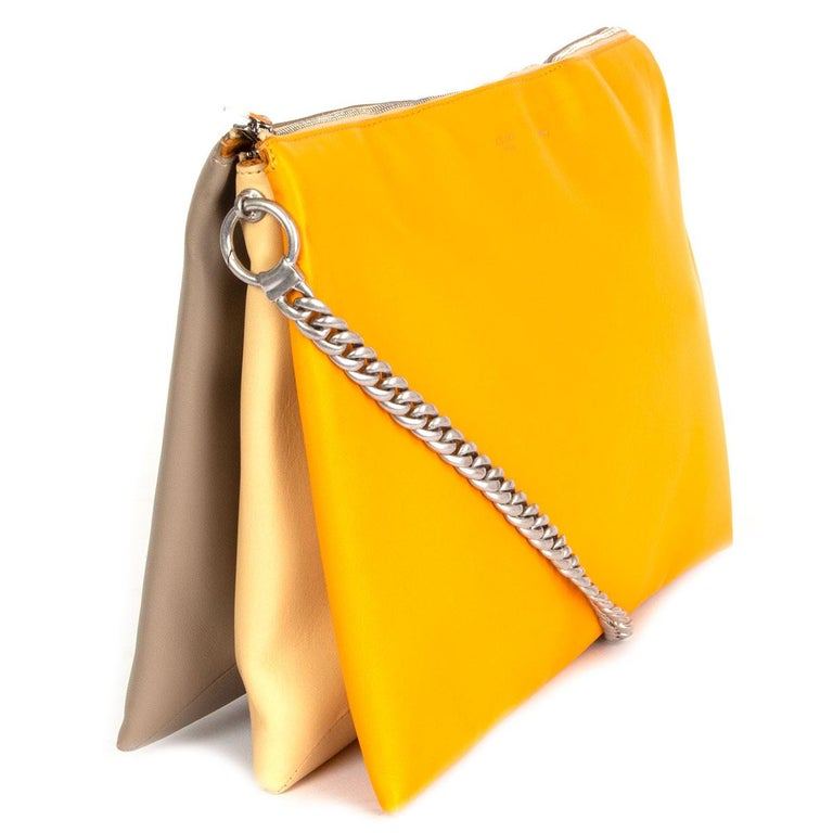 100% authentic Céline 'Soft Trio Chain' shoulder bag in smooth orange, vanilla and taupe calfskin that opens with a zipper on top. Lined in orange suede and divided in three compartments with one big zipper pocket in the middle. Silver-tone metal