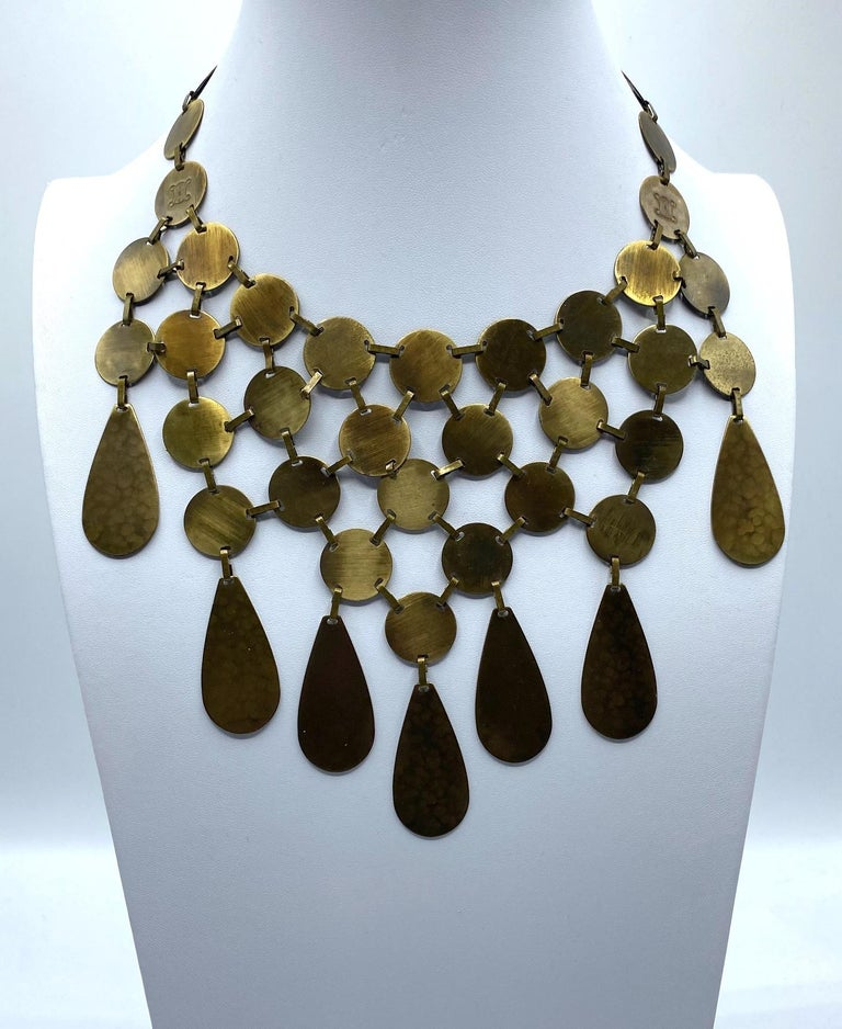 Presented is an amazing Celine bib style necklace in patinated antique bronze finish. It is comprised of .75 of an inch lightly martele' textured antique bronze finished disks with flat band connector links. Along the bottom row are seven pear shape