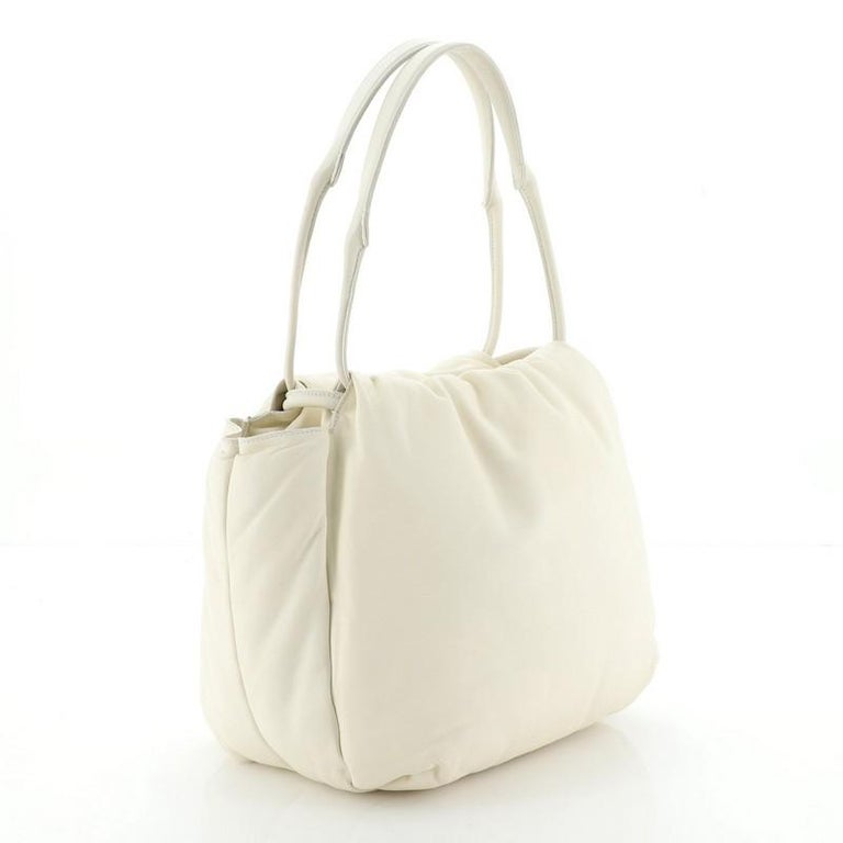 This Celine Pillow Bucket Bag Leather, crafted from neutral leather, features a leather top handle. Its drawstring closure opens to a neutral leather interior with side slip pockets.   Estimated Retail Price: $2,800 Condition: Damaged. Large tear on