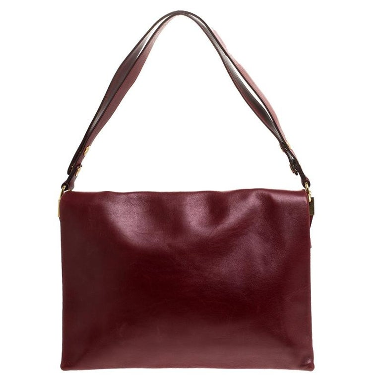 Carry along a mark of sophistication with this simple yet attractive Celine bag. It has been crafted in red calfskin leather. The bag features a top handle and flap closure with blade gold-tone detailing. The interior is leather-lined and has two