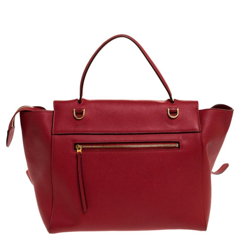 This Celine flap bag is a timeless creation that will never go out of style. Crafted from leather, it comes in a lovely shade of red. It is equipped with a top handle, a front flap that opens to reveal a spacious suede interior with enough space to