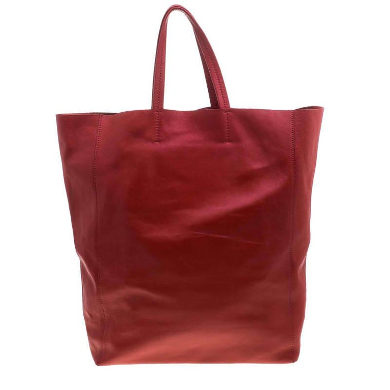 An elegant tote designed by Celine, this Cabas bag is a wonderful mix of fashion and function. Beautifully crafted with red leather into a minimalist yet utilitarian design, the tote features two flat handles and a roomy interior lined with leather