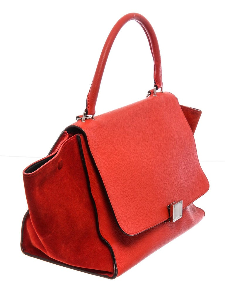 Red leather Céline Medium Trapeze bag with gold-tone hardware, single detachable flat shoulder strap, single rolled top handle, single exterior zip pocket, snap expansions at sides, suede panels at sides, black leather lining, dual interior slit