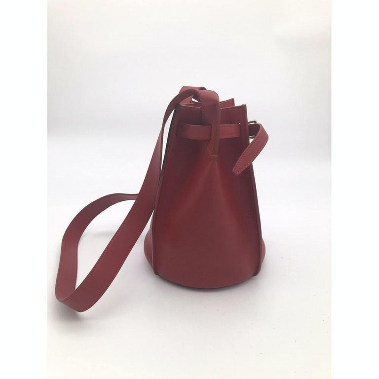 - Designer: CÉLINE - Model: sangle - Condition: Very good condition.  - Accessories: Dustbag - Measurements: Width: 24cm, Height: 23cm, Depth: 20cm, Strap: 94cm - Exterior Material: Leather - Exterior Color: Red - Interior Material: Suede - Interior