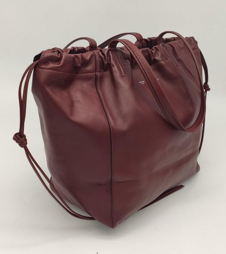 - Designer: CÉLINE - Condition: Never worn.  - Accessories: None - Measurements: Width: 36cm, Height: 29cm, Depth: 16cm - Exterior Material: Leather - Exterior Color: Burgundy - Interior Material: Suede - Interior Color: Red - Hardware Color: