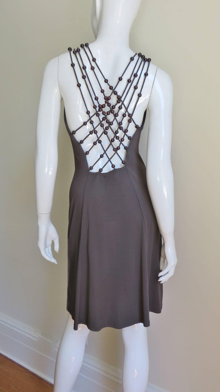 A very chic brown jersey dress by Michael Kors for Celine.  It has rows of brown wooden bead adorned straps at the front neckline which extend over the shoulders to the forming many straps crossing to the low cut back.  The dress gathers and drapes