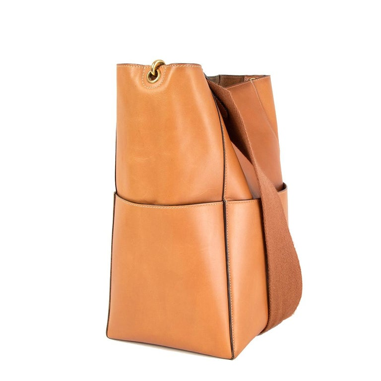 Céline 'Sangle Bucket' shoulder bag in tan natural calfskin featuring gold-tone hardware with four flat outside pockets. Opens with a inner hook closure and is unlined with a flat and zipped pocket against the back. Removable wool shoulder strap.