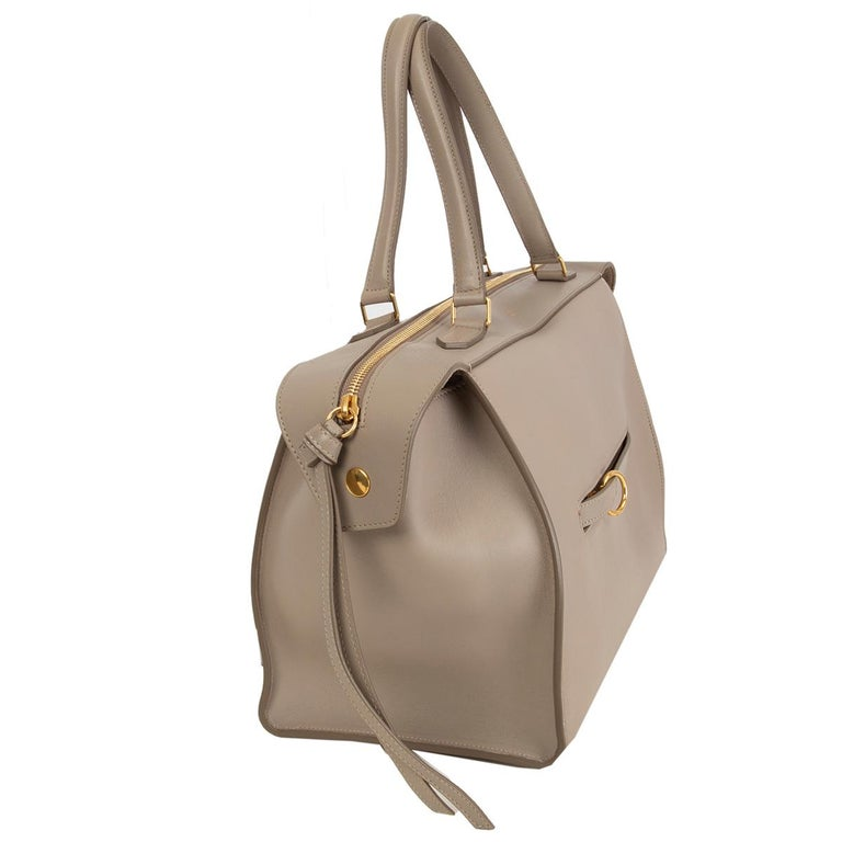 Céline 'Ring' handbag in taupe calfskin with a ring zip pocket at front featuring gold-tone hardware. Opens with a zipper on top and is lined in taupe suede with one zip pocket against the back and two slit pockets attached. Has been carried and is