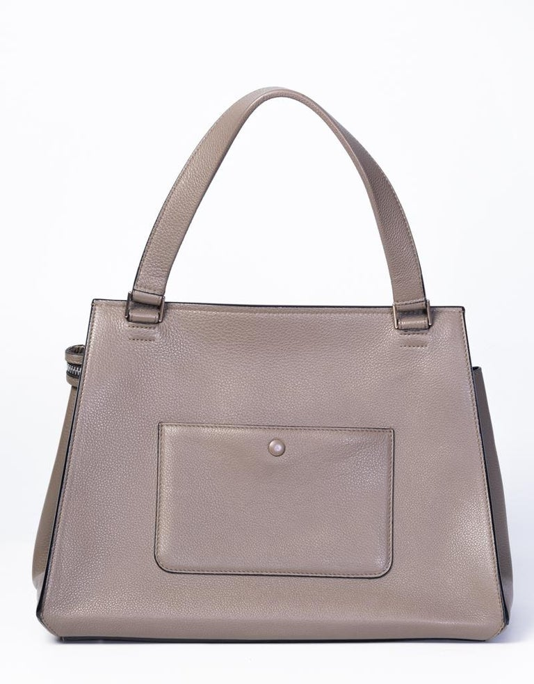 This medium model Celine Edge handbag is made with taupe coloured calfskin leather and features a looping flat leather handle, hardware in silver metal, taupe stitchings, top zip closure, a rear patch pocket with button closure, and black leather