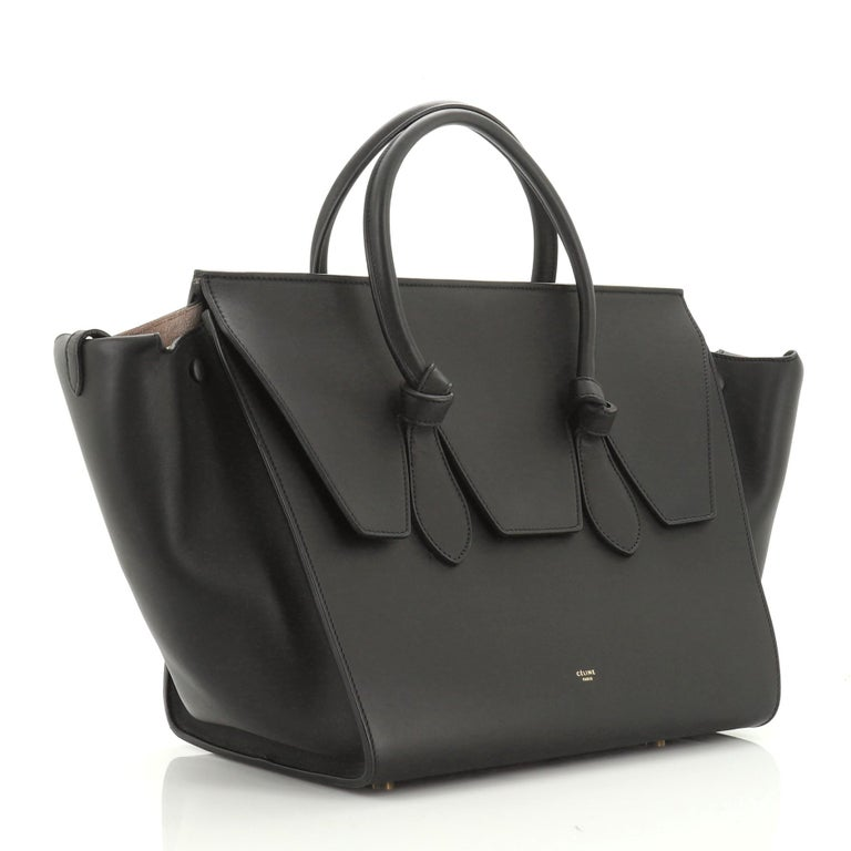 This Celine Tie Knot Tote Smooth Leather Medium, crafted from black smooth leather, features dual rolled leather handles with knot accents, protective base studs, expandable wings, and gold-tone hardware. Its flap that can be tucked inside opens to