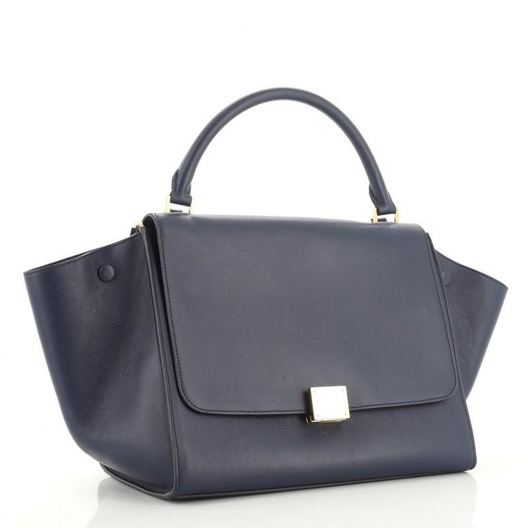 This Celine Trapeze Bag Leather Medium, crafted from blue leather, features a rolled leather handle, exterior back zip pocket, and gold-tone hardware. Its square flip-lock and zip closure opens to a blue suede interior with slip pockets.   Estimated