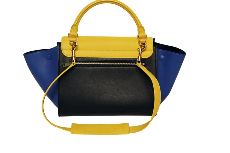 2013 Phoebe Philo's Celine Trapeze handbag made from thick, buttery soft calf skin in striking cobalt blue and bright sunflower yellow. This bag features gold toned hardware, signle rolled leather handle, leather lining with interior pockets and