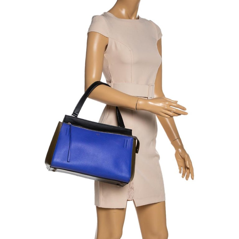 This Celine Edge bag is not only visually magnificent but also functional. It has been crafted from leather and styled with a silhouette that is classy and posh. The tricolor bag has a top handle and a top zipper that reveals a spacious interior.