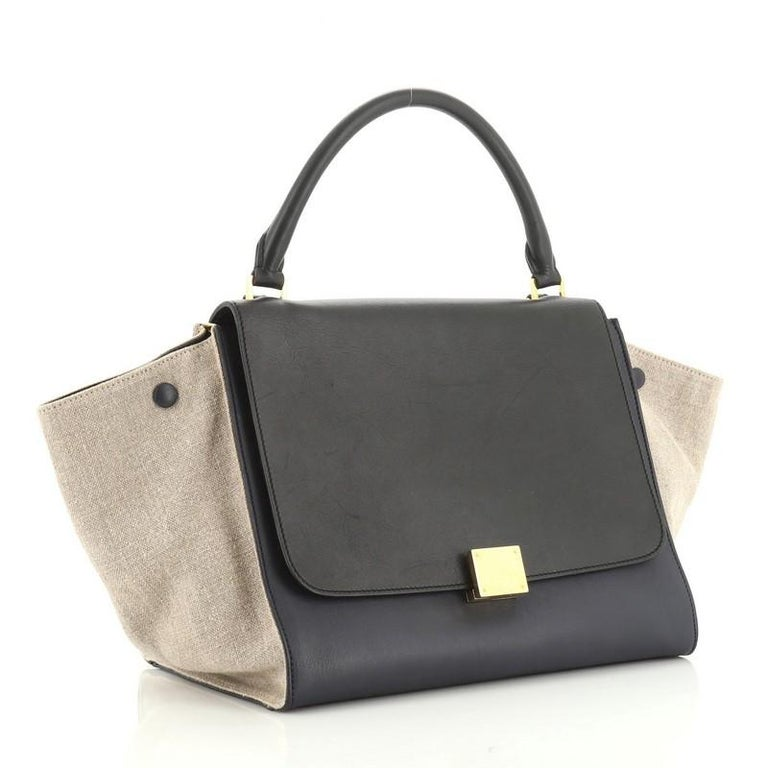This Celine Tricolor Trapeze Bag Leather Medium, crafted from brown and neutral leather, features top looped handle, exterior back zip pocket, side snap closures, and gold-tone hardware. Its square flip-lock and zip closure opens to a neutral fabric