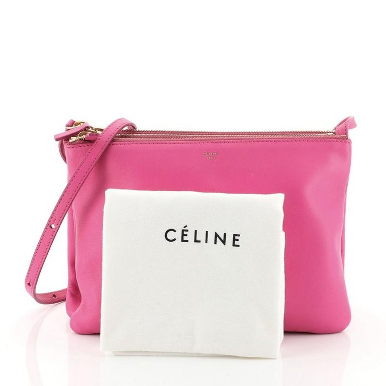 This Celine Trio Crossbody Bag Leather Large, crafted from pink leather, features an adjustable shoulder strap and gold-tone hardware. Its triple zip closures open to a gray jersey interior.   Estimated Retail Price: $1,300 Condition: Great. Minor
