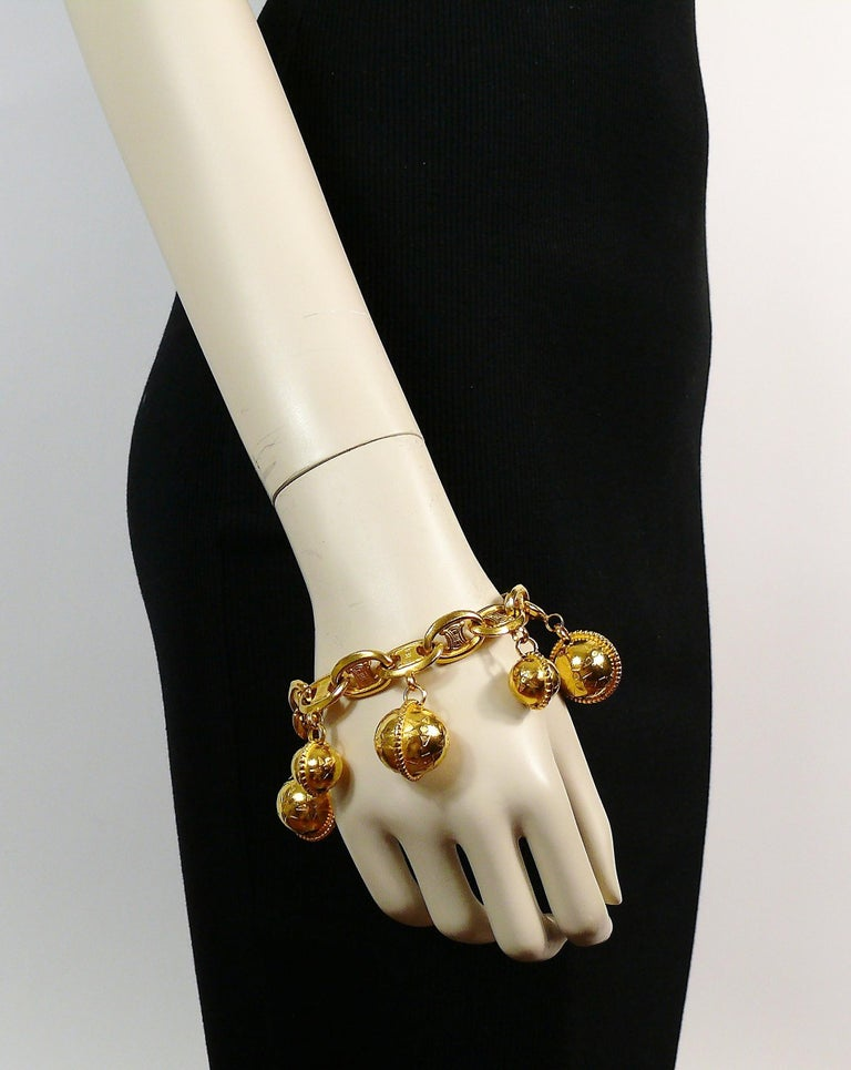CELINE vintage 1990 iconic gold toned bracelet featuring signature links and two-sized planisphere charms.  T-bar and toggle clasp closure.  Embossed CELINE PARIS. Made in Italy 90.  Indicative measurements : length approx. 22 cm (8.66