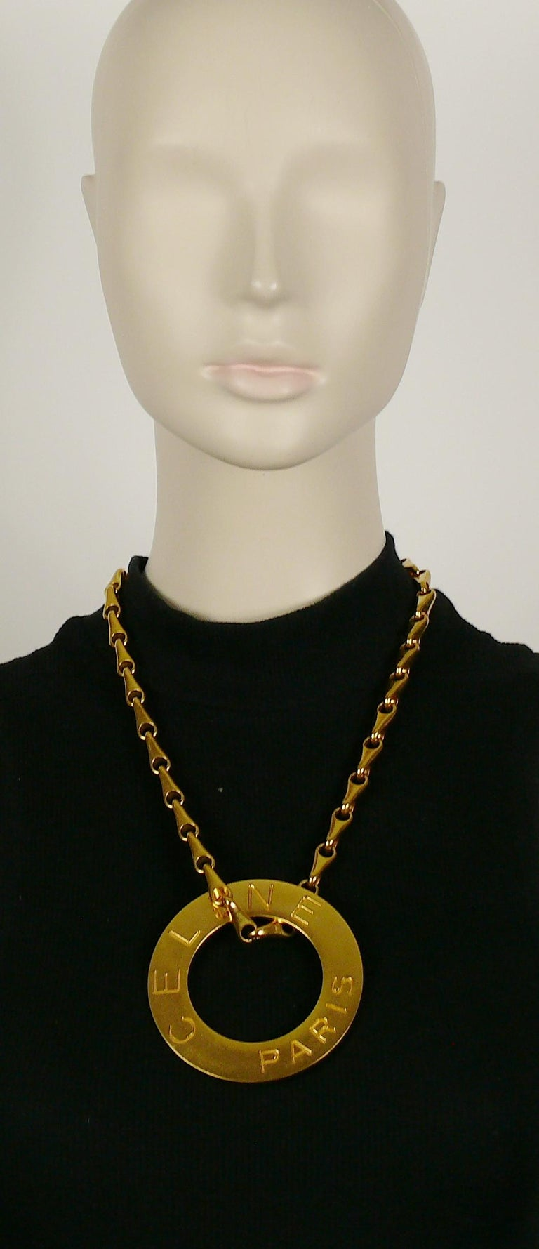 CELINE vintage 1990 gold toned chunky chain featuring a massive disc pendant embossed CELINE PARIS.  Secure clasp closure.  Embossed CELINE PARIS on the clasp. Embossed CELINE PARIS 90 MADE IN ITALY on the reverse of the pendant.  Indicative