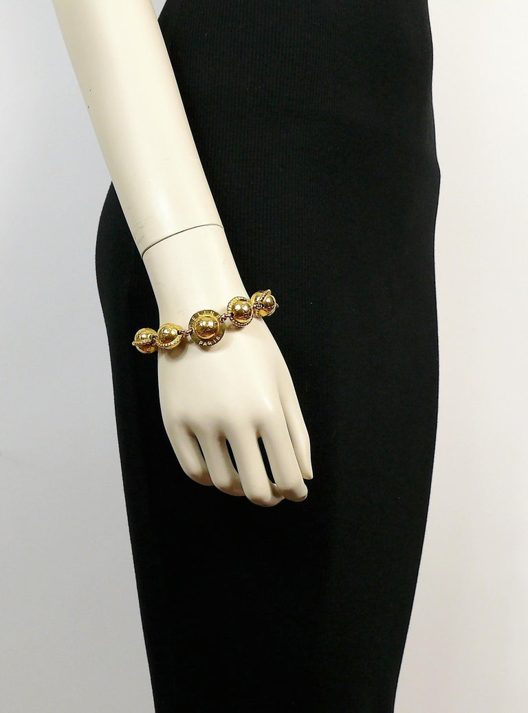 CELINE vintage 1991 iconic gold toned bracelet featuring planisphere links.  Hook clasp closure  Embossed CELINE PARIS. Made in Italy 91.  Indicative measurements : length approx. 21.5 cm (8.46 inches).  Comes with original dust bag (used