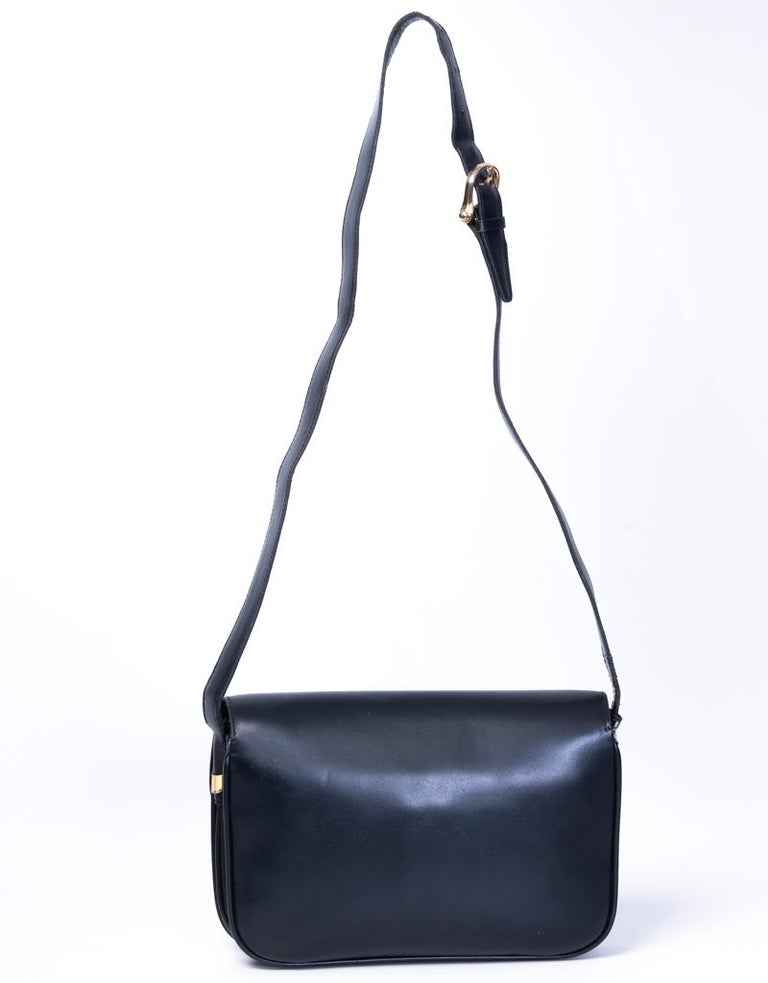 """This vintage Celine crossbody bag is made of black leather and features vintage Celine closure, golden hardware, a front flap a partitioned leather interior with patch pockets.  COLOR: Black MATERIAL: Leather MEASURES: H 6"""" x L 9.5"""" x D 3"""" DROP:"""
