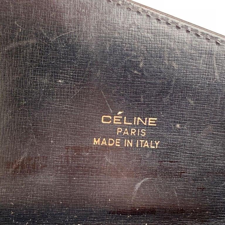 Celine vintage black leather shoulder bag. Flap with gold metal 'Carriage' closure. Leather lining. 2 main sections, with 1 side zip pocket and 1 side open pocket inside. Adjustable shoulder strap. 'Celine Paris - made in Italy' embossed