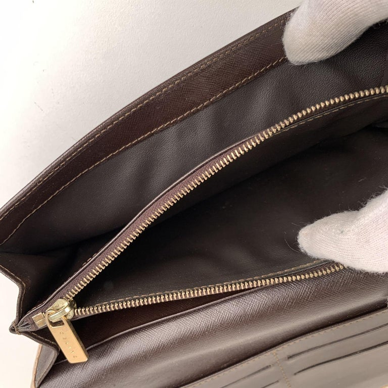 Celine vintage brown Macadam canvas wallet. Flap with button closure. 6 credit card slots under the flap. Inside: 3 main sections (one with zipper closure), 2 side pockets, 4 credit card slots. 1 open pocket on the back.'Celine' engraved on leather
