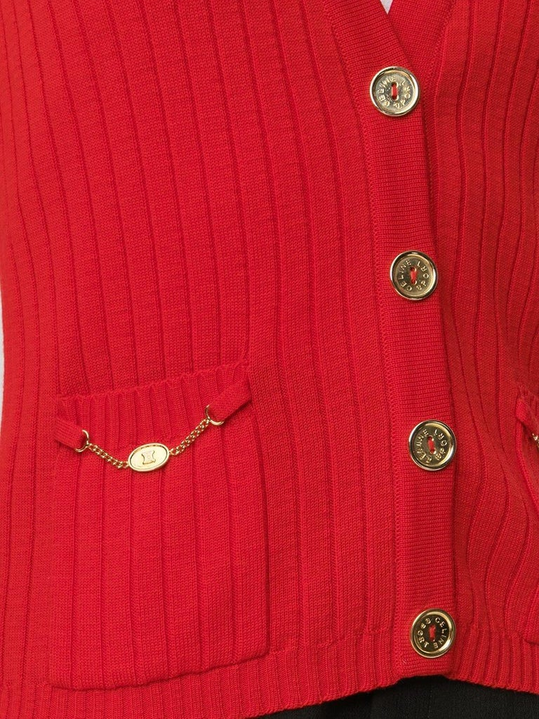 Céline vintage red vest, with V-neck and double front pockets. Featuring gold-coloured engraved buttons, (the internal replacement button is still present.) and small golden chains on the pockets.  Colour: Red/ Gold  Composition: 100%