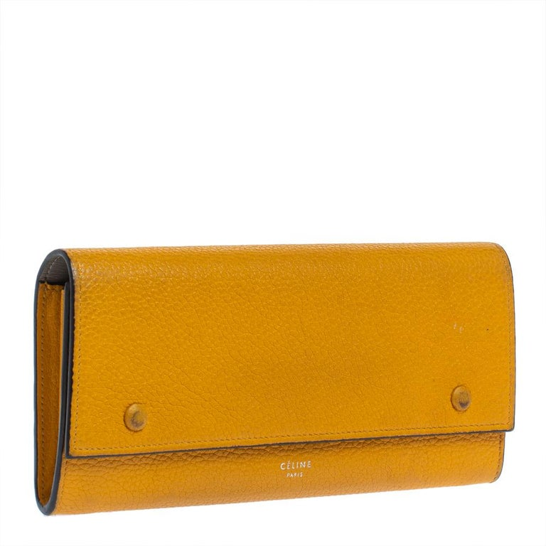 Designed to perfection from leather, this wallet will be your go-to accessory. From the house of Celine, it features a front flap accented with snap button fastening along with multiple card slots and a zip pocket. Adorned in a yellow shade, this