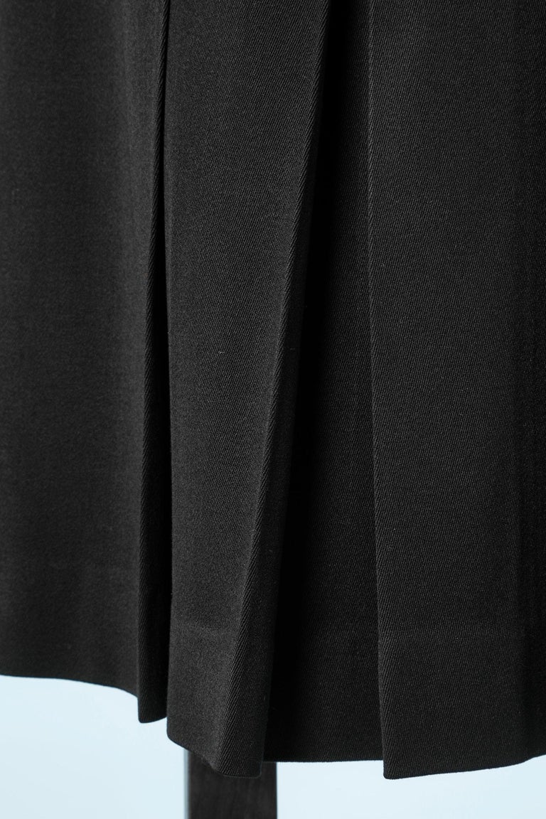 Pleated knee lenght skirt in black wool with belt effect in leather and gold metal