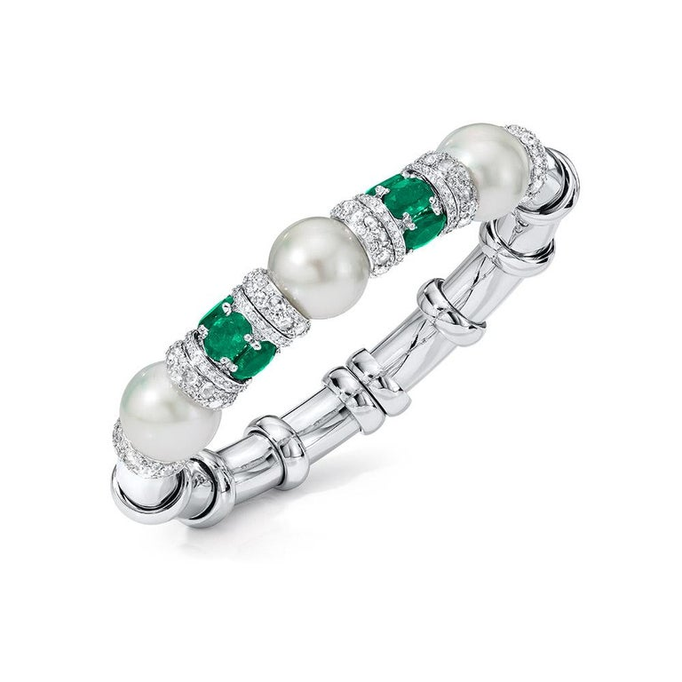 This elegant bracelet is set with 3 South Sea pearls and 6 oval-shaped Emeralds , accented with Diamond rondelles; set in 18-karat white gold. Flexible with open back. Diamond weight: approximately 2.89 carats total. Emerald weight: approximately