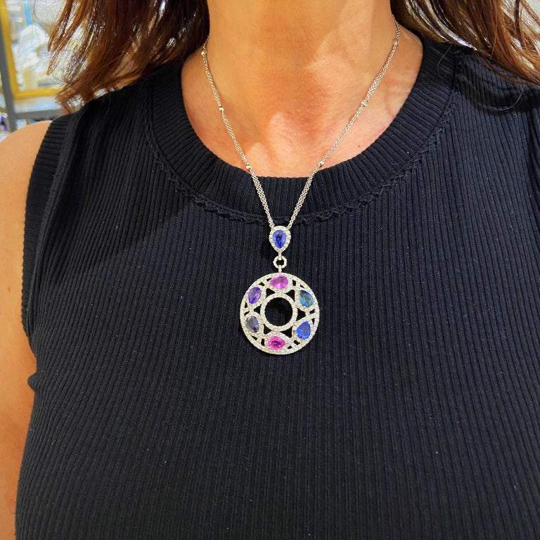 A magnificent 18 karat white gold and Diamond pendant. The pendant is set with round brilliant Diamonds in an openwork setting. Seven pear shaped Sapphires in shades of Purple, Pink and Blue are the centerpiece of this pendant. The pendant and bale