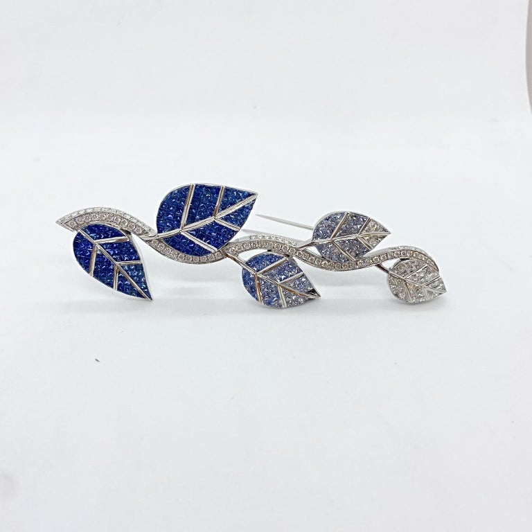An extraordinary set 18 karat white gold , Diamond and Blue Sapphire leaf brooch. Each of the five leaves are invisibly set with Princess Cut stones. The top leaf starts in all white Diamonds slowly following to shaded colors of Blue Sapphires . The