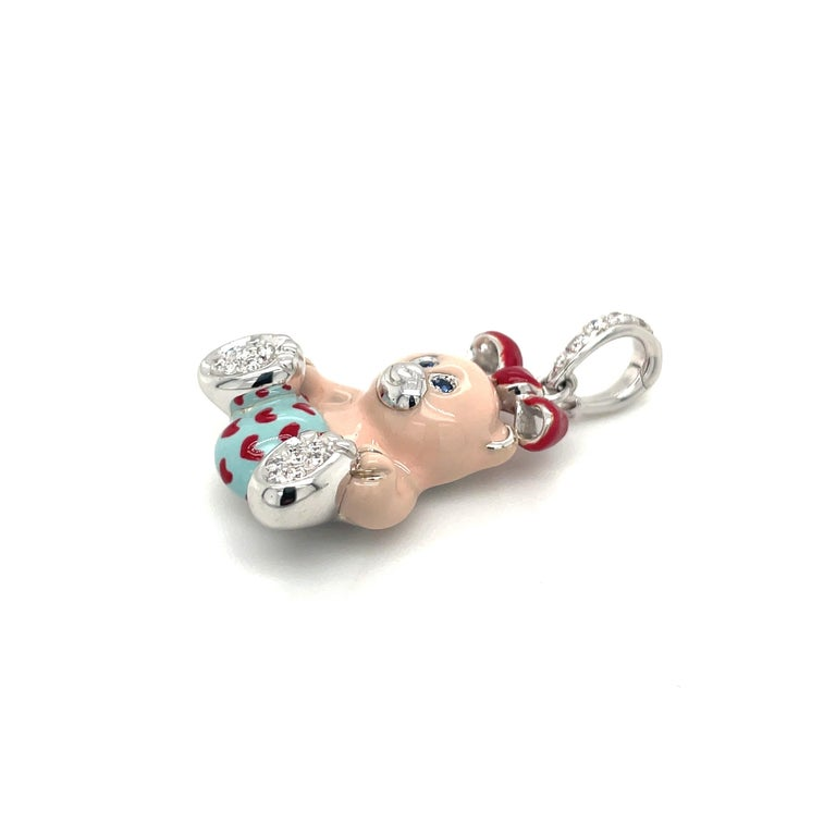Just the cutest....Teddy bear charm made exclusively for Cellini by Ambrosi of Italy.  This 18 karat white gold teddy bear is set with round brilliant pave diamonds on her paws . She has blue sapphire eyes . Her body is light pink enamel and her