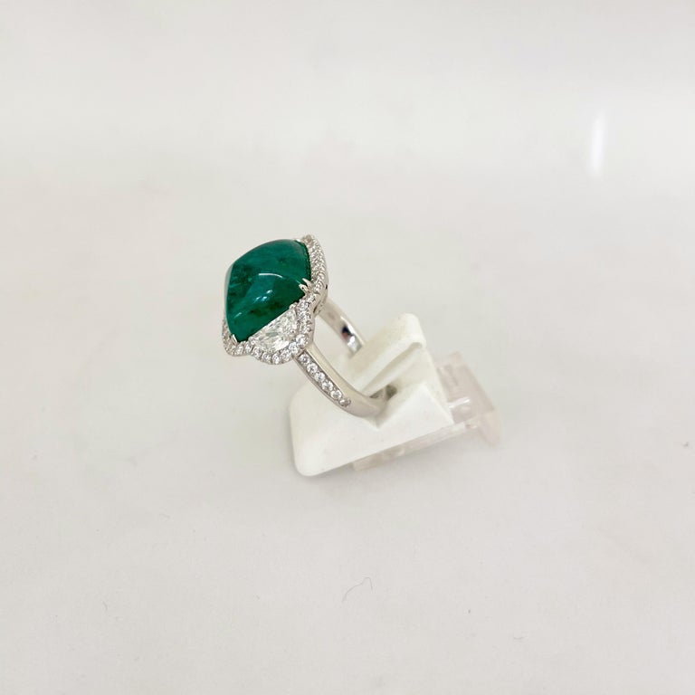 This truly show stopping sugarloaf cabochon emerald is flanked by half-moon diamonds and surrounded by a micro-pave diamond bezel, with diamonds on the shank of the ring.  The emerald is 10.58 ct  Half moon diamonds total 0.84cts  Round diamond