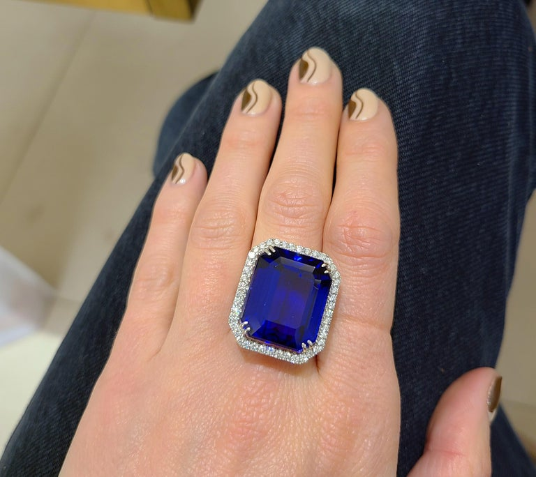 This amazing emerald -cut tanzanite center stone ring  is edged with round brilliant-cut diamonds and diamonds along 3/4 of the shank. Set in 18-karat white gold. Diamond weight: approximately 1.45 carats total. Tanzanite weight: 32.27 carats. Ring