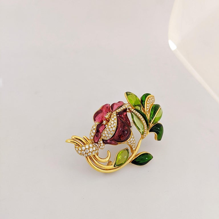 This intricate 18 karat yellow gold flower brooch was made exclusively for Cellini in Italy by Roberto Casarin. Hand carved Rubelite stines  in different shades of pink are set as the petals, along with Green Chrome tourmaline as the leaves. The