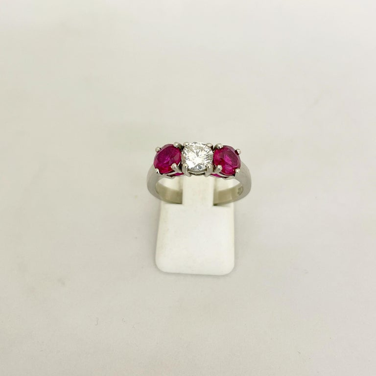 Classic 3 stone platinum ring. This ring centers a round brilliant diamond weighing 0.61 carats. The center diamond is flanked by 2 round brilliant rubies with a total weight of 1.63 carats. Finger size 6-3/4 sizing available Appraisal upon request