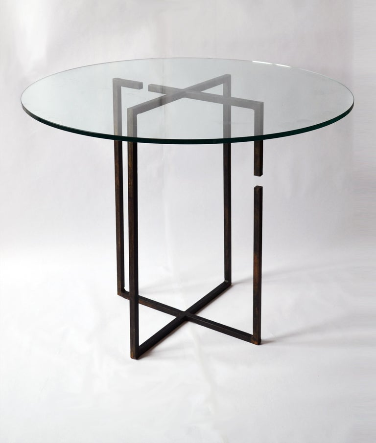 """Center table No. 4 by JM Szymanski Dimensions: L 22"""" x SW 22"""" x H 30""""   36"""" diameter glass top at ¾"""" thick Materials: Blackened waxed steel, ultra clear glass  Inspired by two repelling magnets, this table is unique in its form and structure."""
