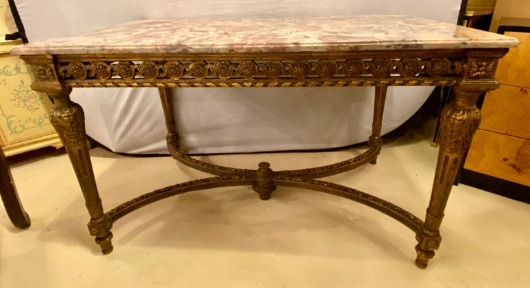 Stamped Jansen center table having a gilt base and fine pink, grey and white veined marble-top. The top having been professionally repaired. The Louis XVI style center table having been antique guided. The four corner legs supported by X-form carved