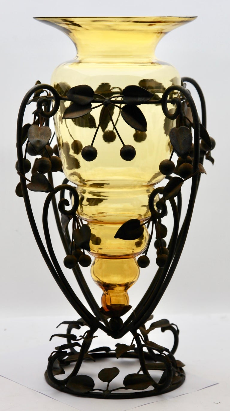 Table centrepiece vase with a large amber glass vase in the original supporting stand.  This Art Deco style glass vase has a wrought metal frame with organic swirls, tree branches and leaves with cherries, in the style of Louis Majorelle. The