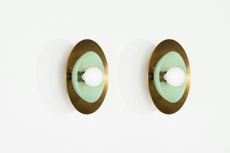 The centric wall sconce is a stately take on French modernism, featuring a spun metal mesh shade nestled into a large solid brass bowl. A substantial, handsome piece that works well in both modern and transitional interiors. Centric pays homage to