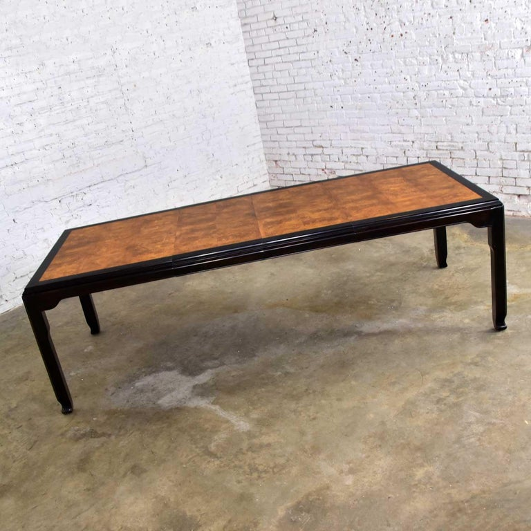 Fabulous Hollywood Regency Chinoiserie dining table designed by Raymond K. Sobota for his Chin Hua Collection for Century Furniture. Comprised of an ebonized dark brown frame with burl wood inset. Beautiful vintage condition. The framework of the