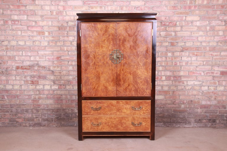 An exceptional Mid-Century Modern Hollywood Regency Chinoiserie gentleman's chest or armoire dresser  By Raymond Sobota for Century Furniture  USA, 1970s  Burl wood, with ebonized trim, and original Asian-inspired brass hardware.  Measures: