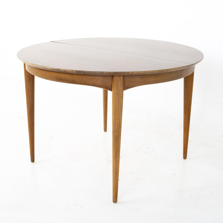 Century Furniture Mid Century round oval expanding walnut dining table Table measures: 44 wide x 44 deep x 29.25 inches high; each leaf is 12 inches wide, making a maximum table width of 68 inches when both leaves are used   All pieces of