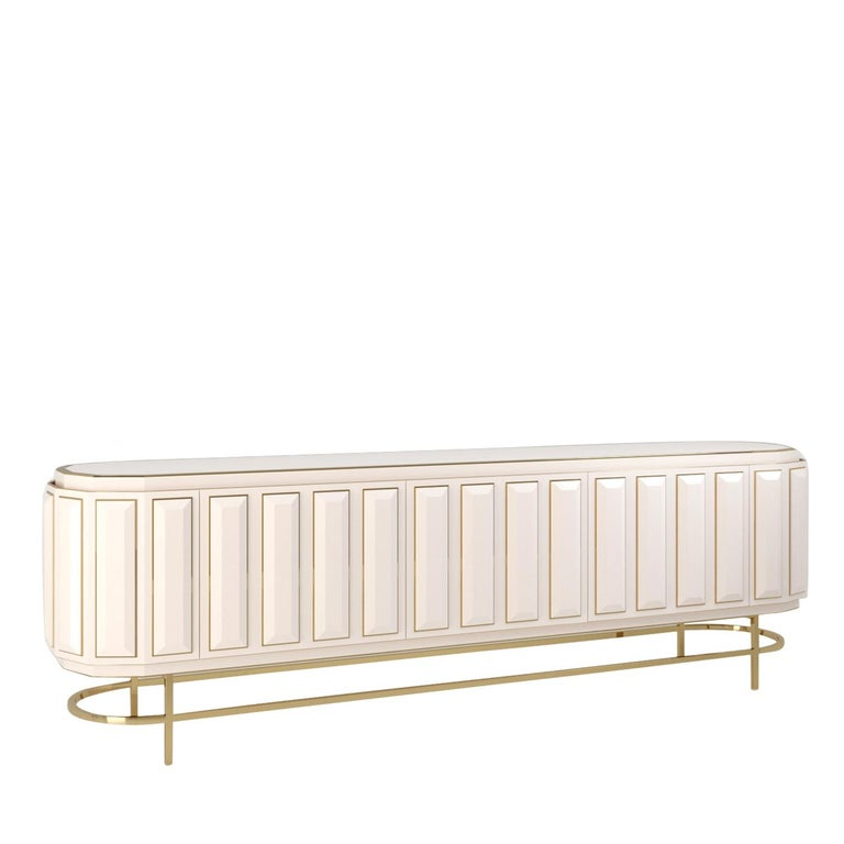 Boasting a lavish white leather upholstery, this sideboard will make a statement in any polished interior. The load-bearing frame is constructed of wood and its elliptical shape is highlighted by the gold-finished metal base that also includes four
