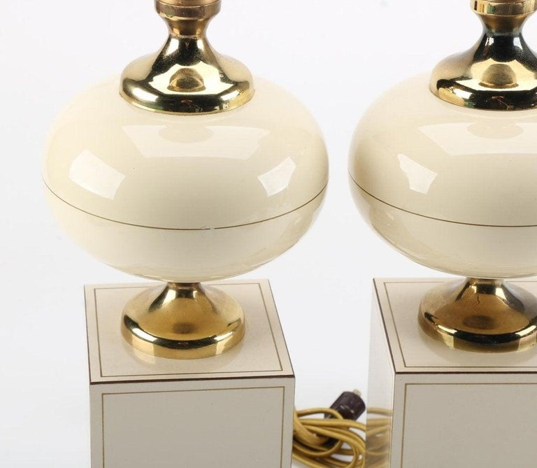 A pair of vintage table lamps with brass accents.   This selection includes a matching pair of table lamps with gold toned sockets and a curvaceous brass neck, font CAP, and rectangular base.  The bipartite body of each is comprised of an ovoid