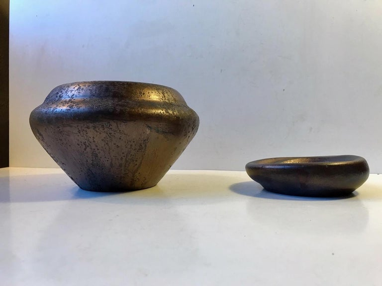 Vase and small matching dish from the workshop of Soren Kongstrand. These pieces are designed by his colleague and apprentice Jens Petersen. Both are unique pieces from circa 1935 and signed JP. Experimental glazes: metallic/copper based luster